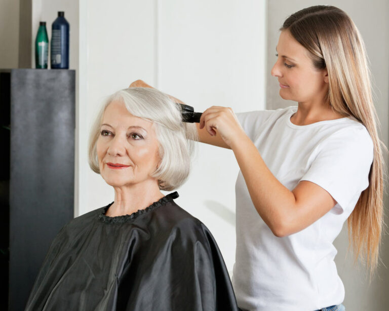 Gaines Park Senior Living   Caregiver styling senior woman's hair